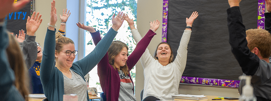 Students in class with hands in the air